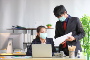 Manager and secretary are working in business office while wearing medical face mask for protecting and preventing the infection of corona virus or covid-19